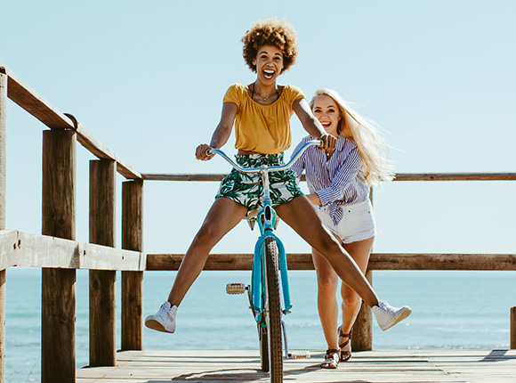 two friends biking on the pier