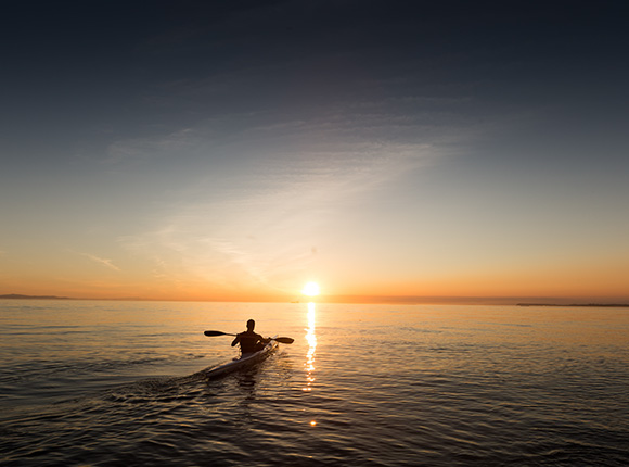 man kayaking in the bay at sunset