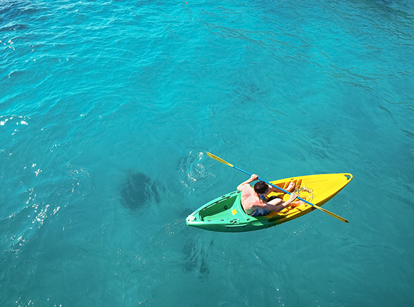 man kayaking in the middle of the ocean