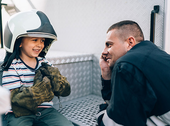 firefighter talking to a little boy