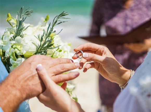 woman placing a wedding band on her grooms hand