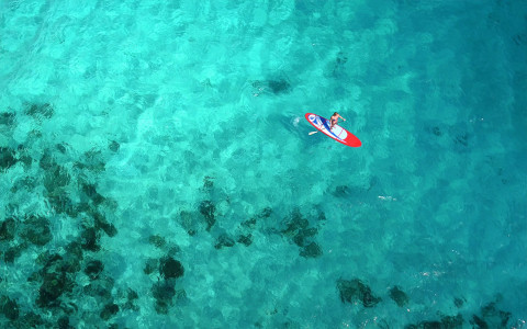 birds eye view of someone kayaking on a crystal clear water