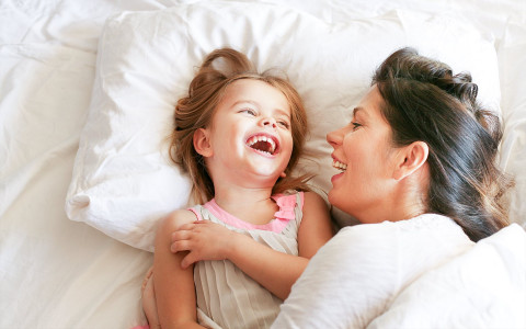 mom and daughter playing on a bed
