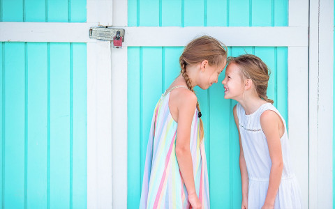 little girls standing against a bright blue wall