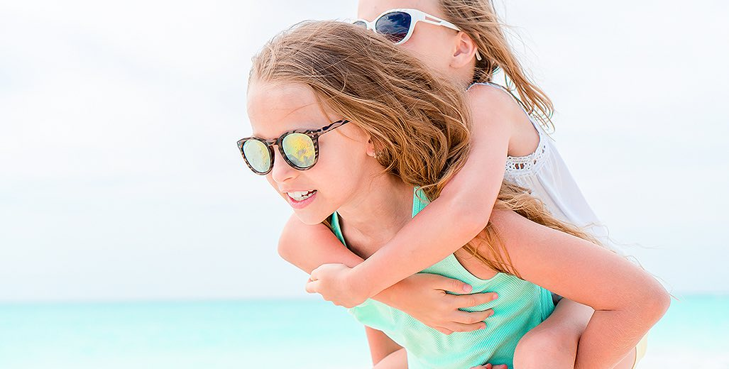 sisters piggy backing on the beach