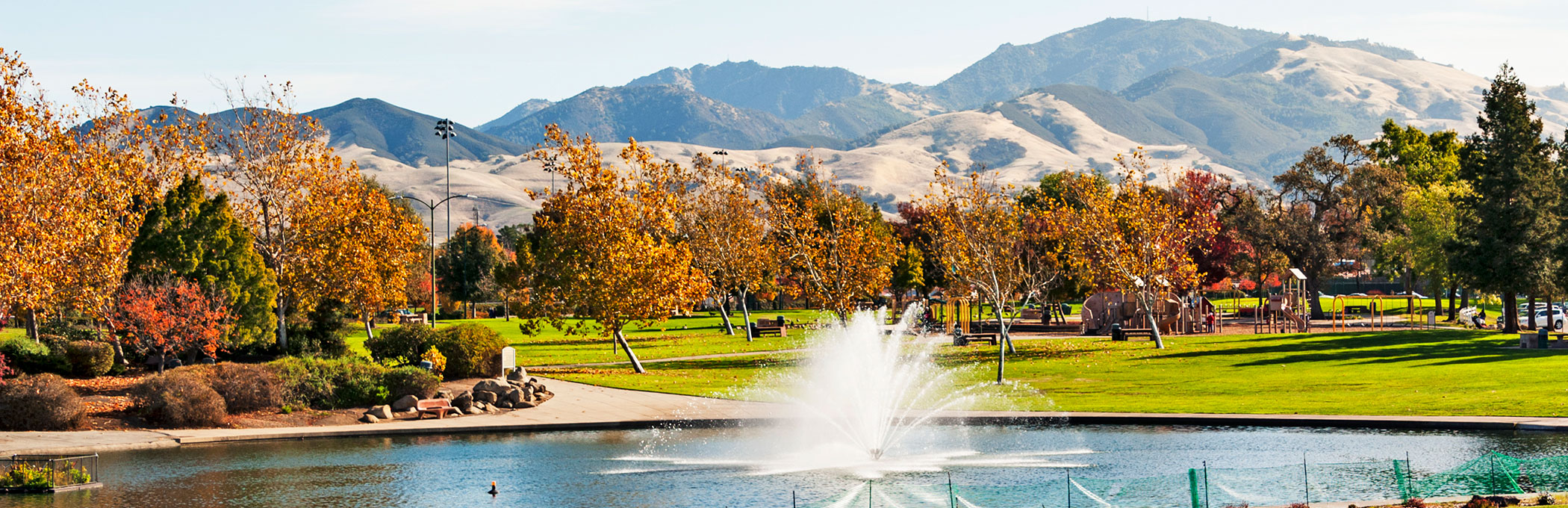 Lake with water fountains & autumn trees in the back