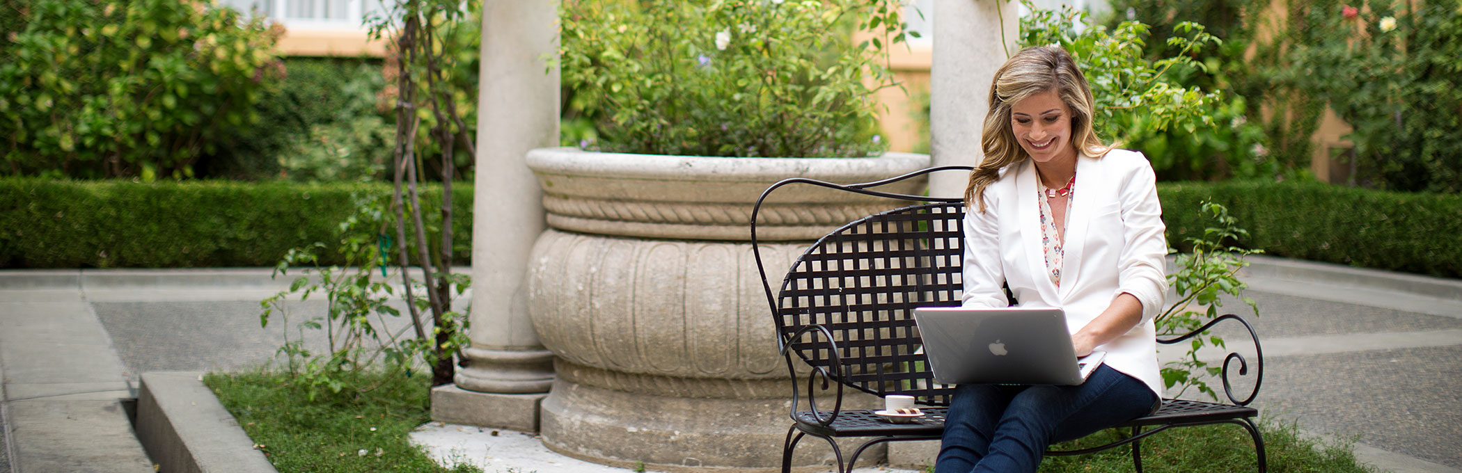 woman on macbook outdoors