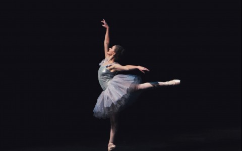 Ballerina standing on single tiptoe with other limbs extended against black background