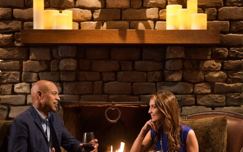 couple drinking and conversing in front of the fireplace
