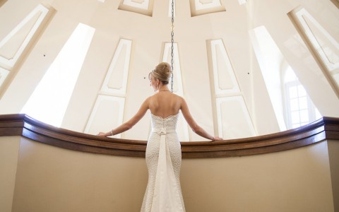Bride standing on indoor balcony