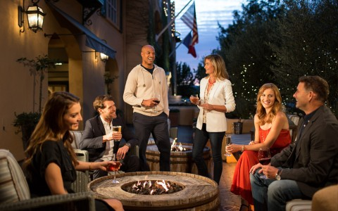 Group of people drinking wine around outdoor fire pit