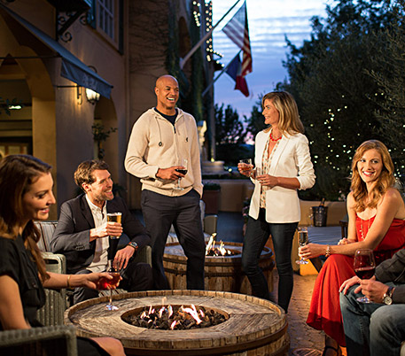 friends around a fire pit enjoying wine
