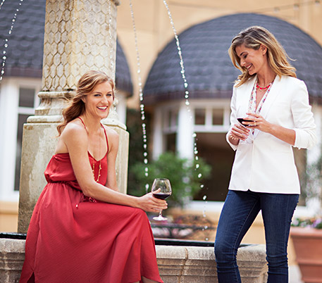 Two women drinking wine next to water fountain