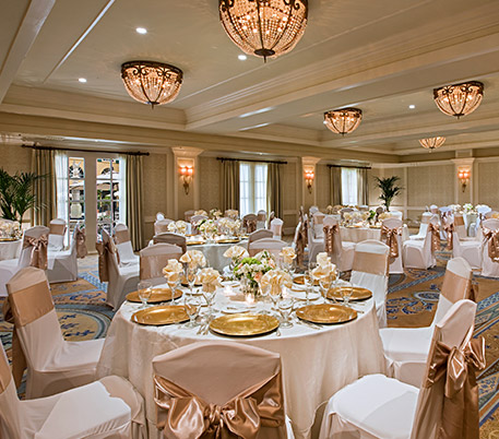 Room with round tables set with white table clothes & golden plates