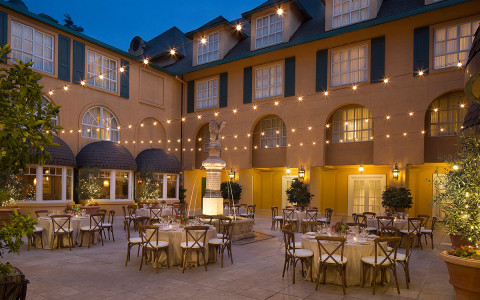outdoor courtyard area with tables and chairs with place settings on the tables and string lights above them