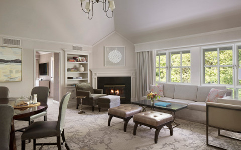 a cream colored room with a sofa, a fireplace, a table and chairs