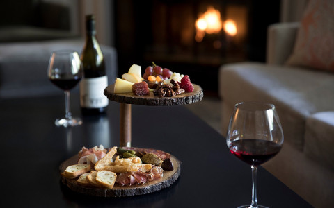 wine glasses filled with wine next to a wood platter that is holding cheese, fruit and crackers