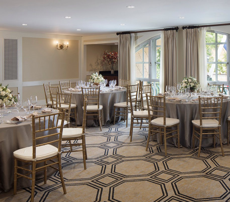 a room with a cream patterned floor, round tables with chairs around them and place settings, glasses, and floral arrangements on the tabless