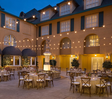 tables and chairs in a courtyard underneath string lights