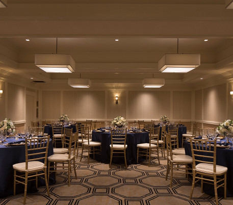 a ballroom with chairs around tables with blue linens, place settings and flower arrangements on the tables