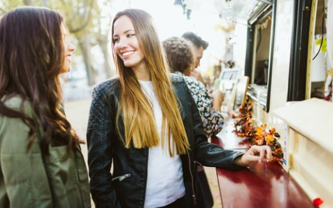two girls at food truck in the fall