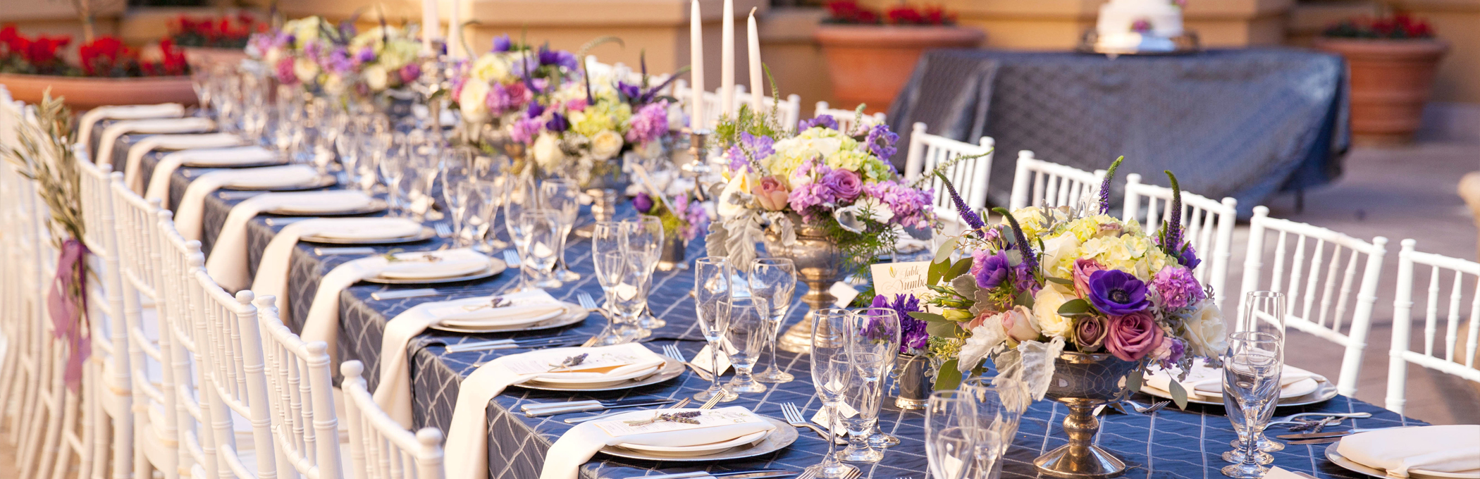 a long table with place settings and purple flower arrangements