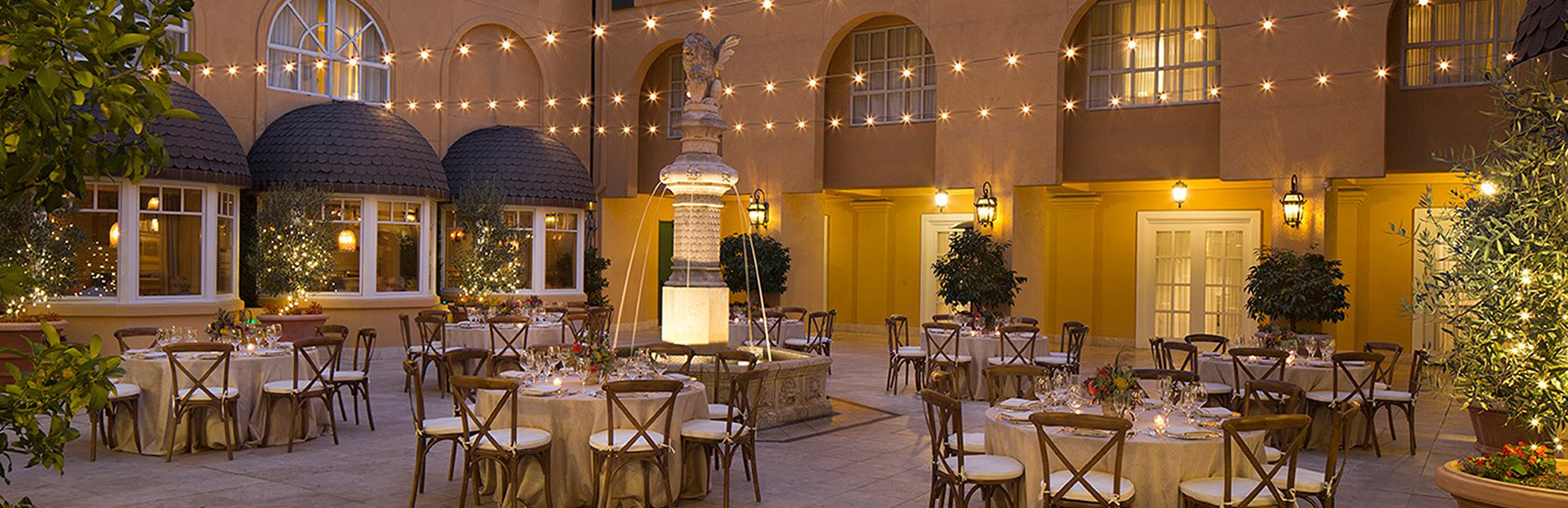 courtyard with tables and chairs sitting below string lights
