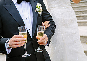 a man in a suit holding two drinks in his hand next to a bride