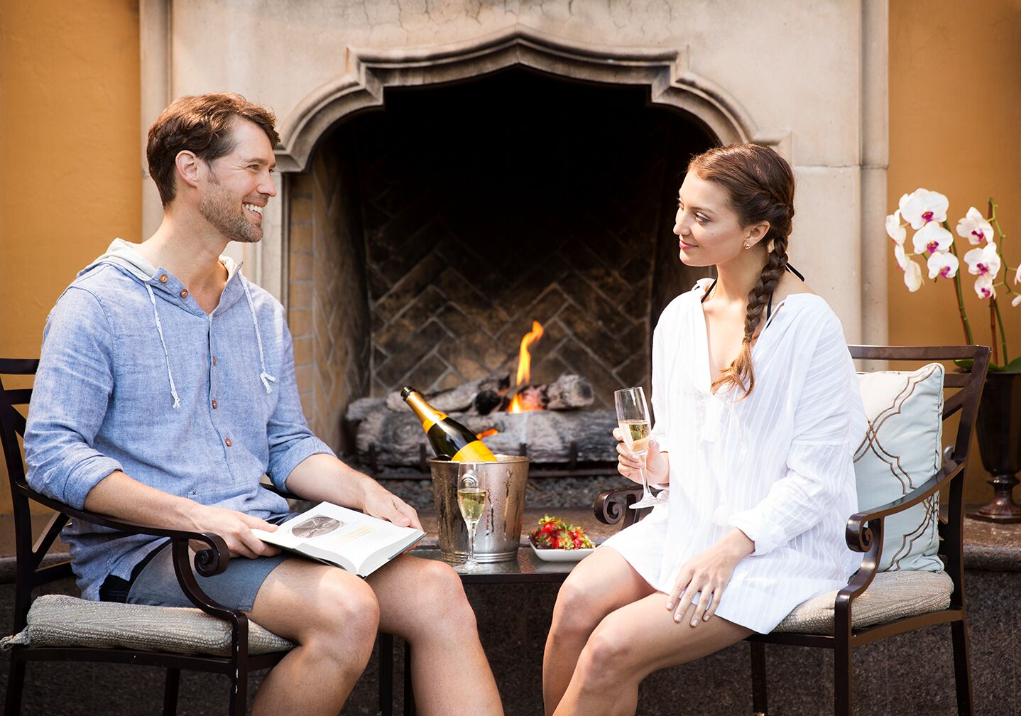a man with brown hair wearing a blue longsleeved shirt talking with a woman with a long braid and a white dress in front of a fireplace with a glass of champagne in her hand