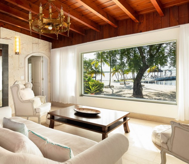 Living room area with white couches all facing a large window that looks towards the marina