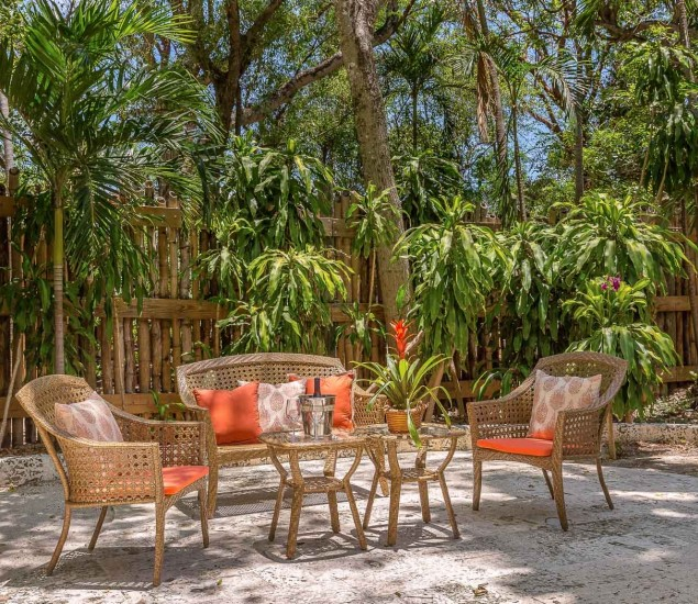 patio area with long wicker chairs and red cushion pillows