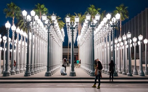 people walking through the street lamp display at LACMA