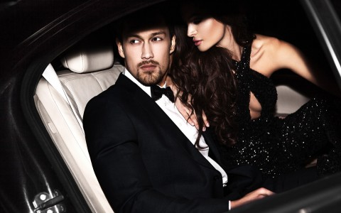 woman in black dress sitting closely to man in suit, while in a car