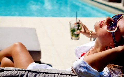 woman in sunglasses holding a drink by a pool