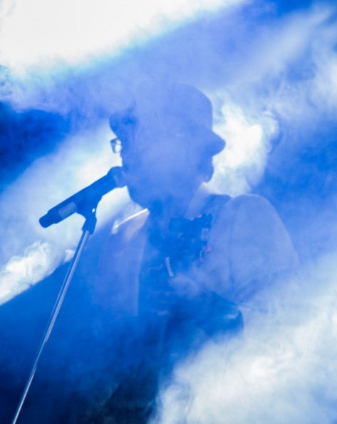 Musician at microphone obscured by smoke and blue strobe lights