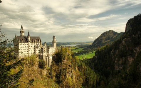 Neuschwanstein Castle and surrounding greenery of Alps beneath a cloud spattered sky