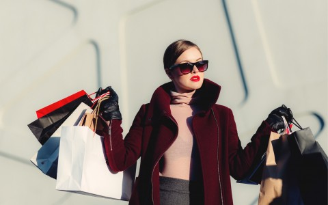 fashionable woman in a jacket and sunglasses shopping