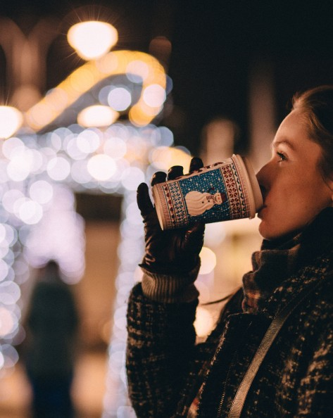 Woman dressed in scarf coat and gloves drinking coffee from holiday cup in front of illuminated Christmas display