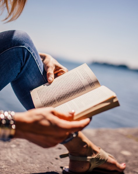 Woman sitting by water wearing denim jeans and holding open a book