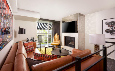 living room area of the superior two queen bed suite with brown lether couches and funky gold hand shaped chair