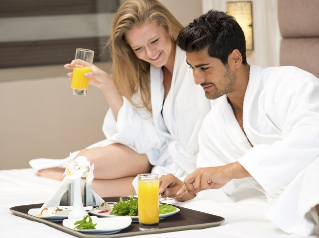 coupld having breakfast in bed in bathrobes