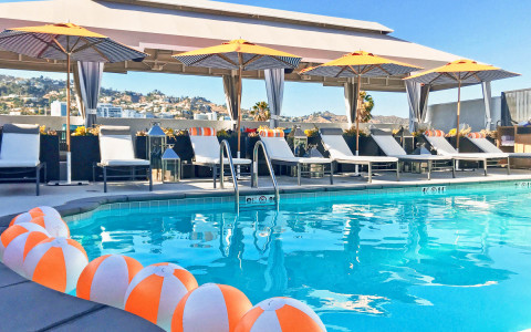 rooftop pool with beach balls in the water and a view of west hollywood