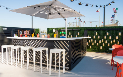 outdoor bar at the pool in front of a wall of greenery with colorful drinks lined up
