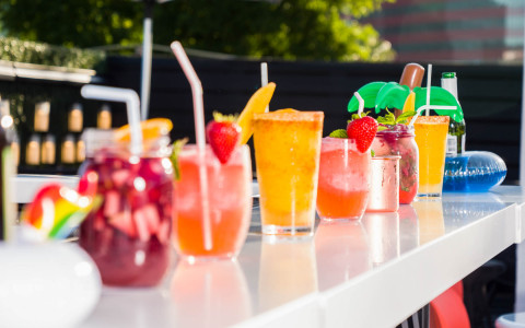 colorful cocktails lined up on the outdoor pool bar