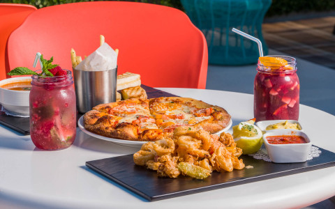 al fresco dining at the pool area with calamari pizza french fries and two cocktails
