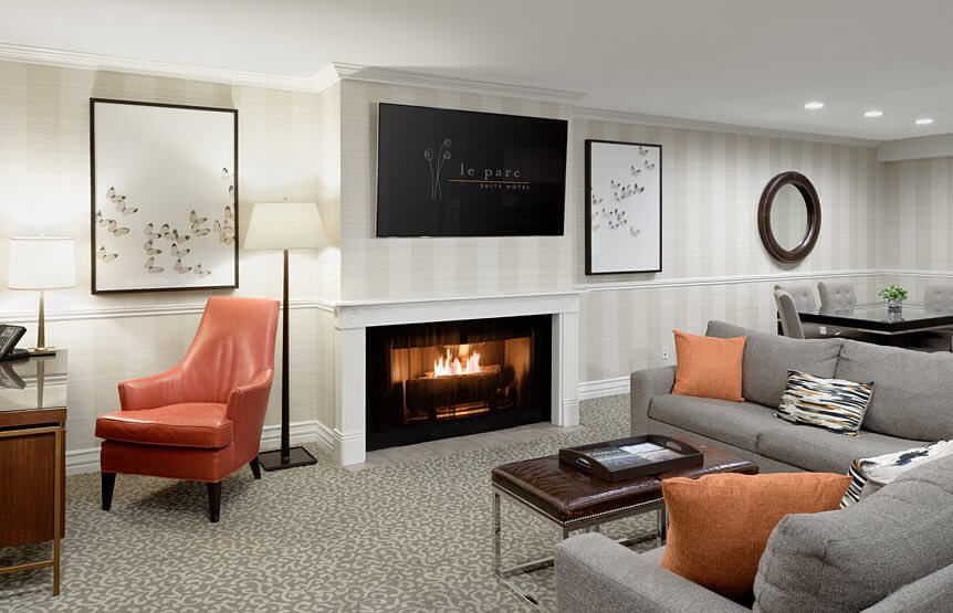 Living room space with TV, fireplace, couches, chair, and coffee table