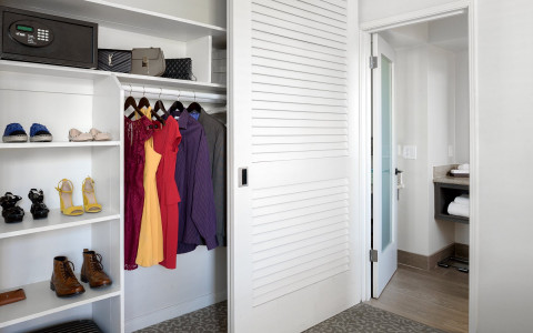 Closet half opened with clothes hanging