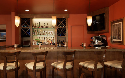 Bar area with barstools and liquor shelves