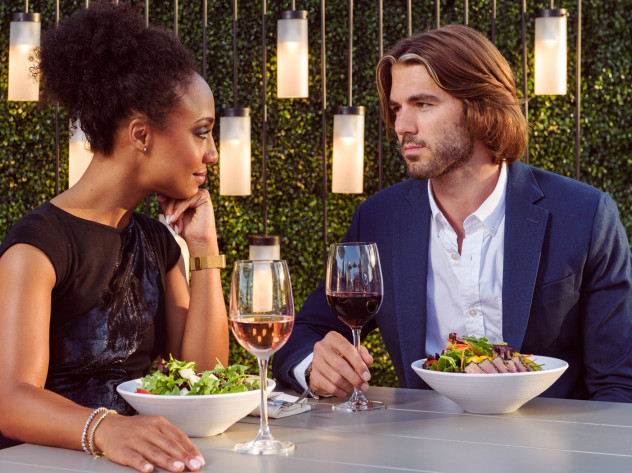 Man and woman sitting at table with food and drinks