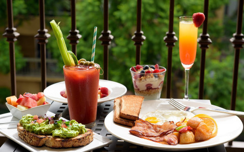 Patio table filled with assorted breakfast foods and alcoholic drinks